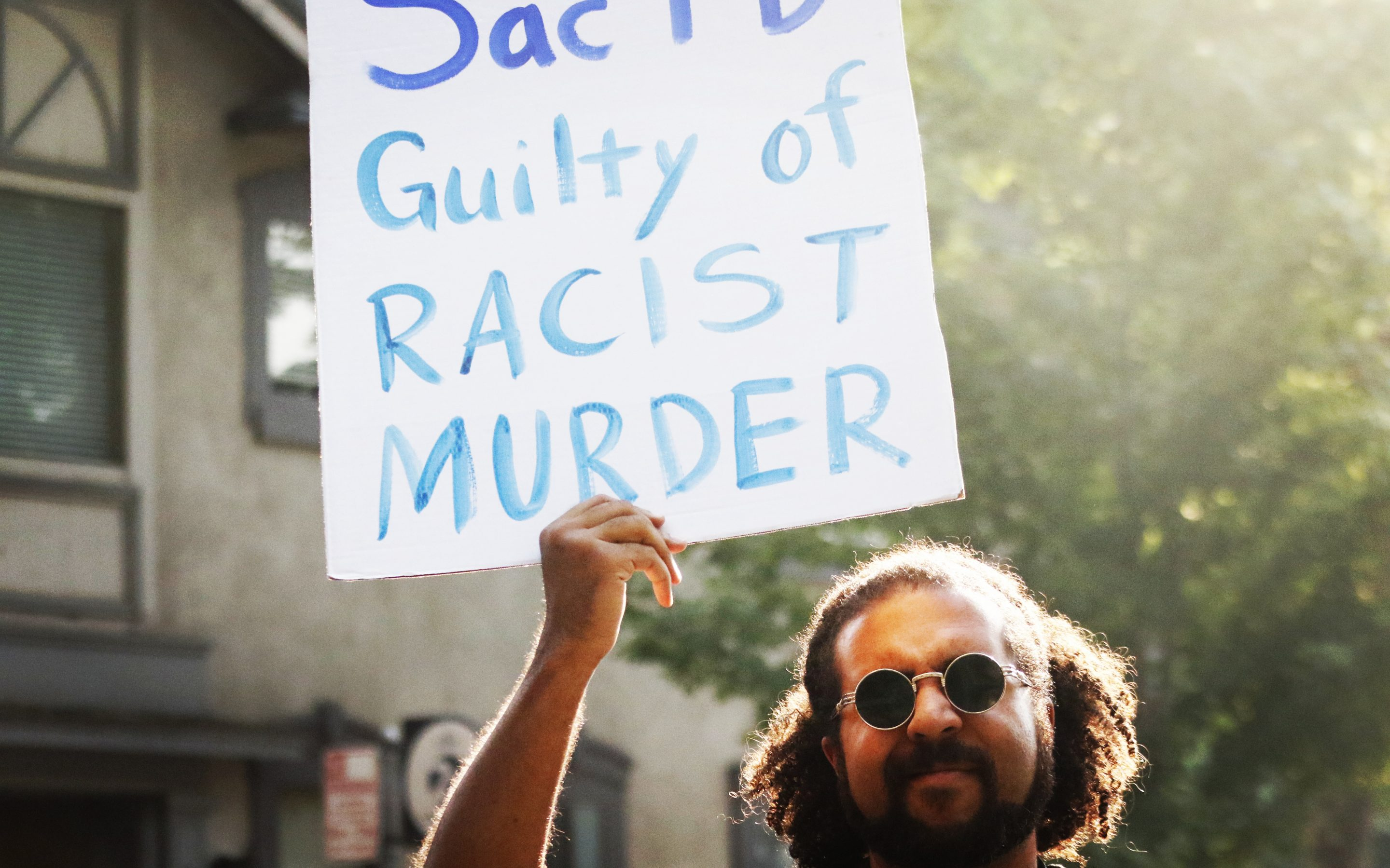 """BLM Member holding sign that reads: """"Sac PD Guilty of Racist Murder."""""""
